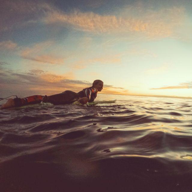 Frau im Meer auf Surfbrett beim Sonnenuntergang.