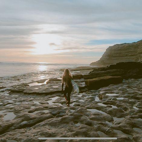 Frau mit Surfbrett am Meer.