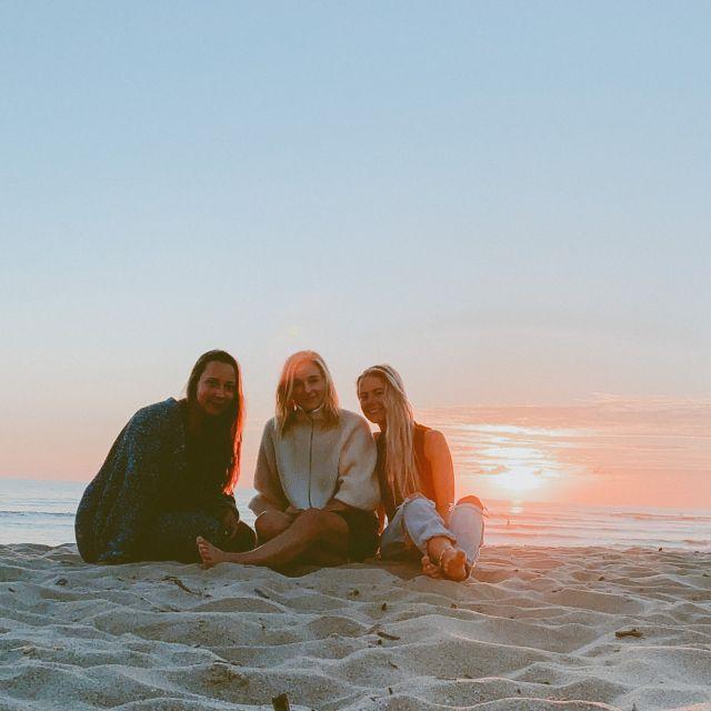 Drei Freundinnen am Strand beim Sonnenuntergang.