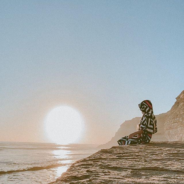 Frau auf Klippe bei Sonnenuntergang.