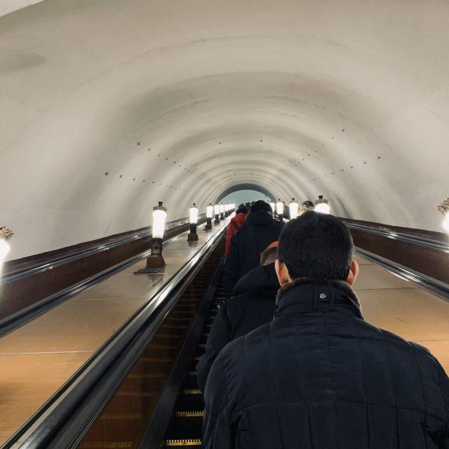 Eine lange Rolltreppe bringt Menschen zu den Haltestellen.