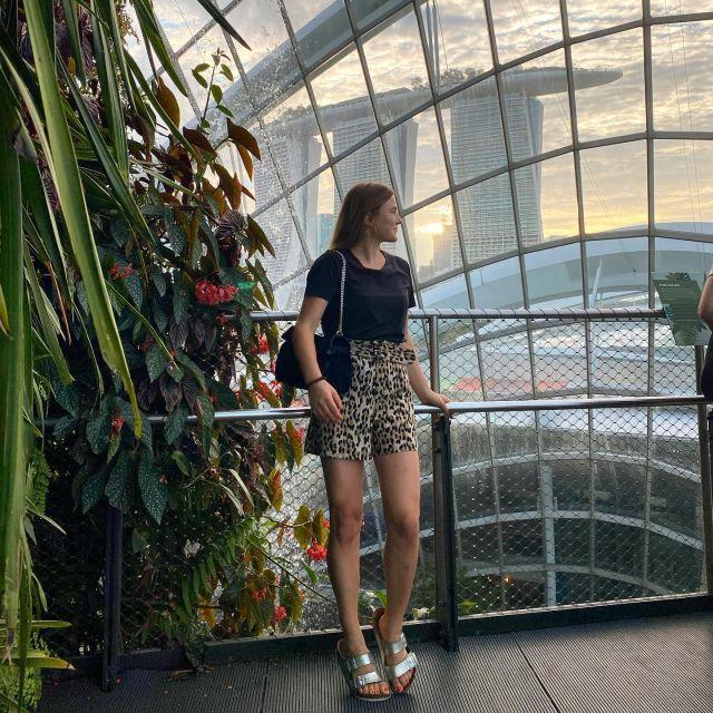 Sophia schaut aus einem Fenster auf die Skyline von Singapur.