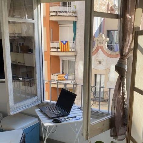 Ein kleiner Tisch der mit einem Notebook an einem Fenster steht.