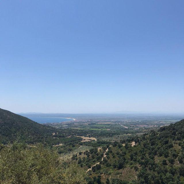 Ausblick über eine hügelige Landschaft, mit dem Meer im Hintergrund.