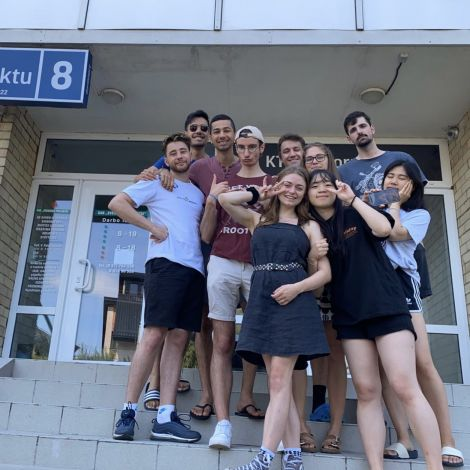 Zehn Freunde stehen auf der Treppe vor dem Wohnheim acht in Kaunas