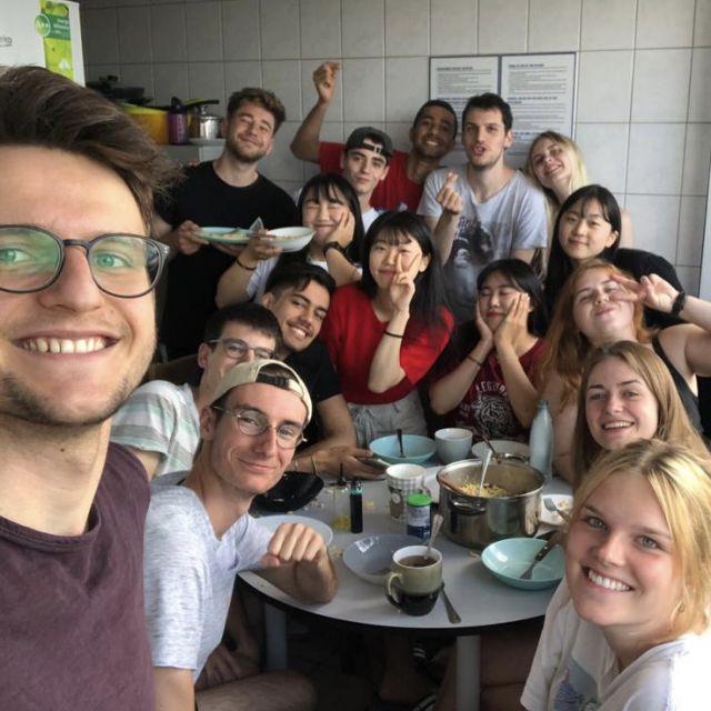 Viele Freunde als Selfie mit Spaghetti auf dem Tisch in der Wohnheimküche