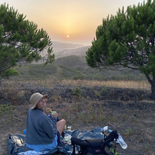 Frau unter Nadelbäumen mit Sonnenuntergang.
