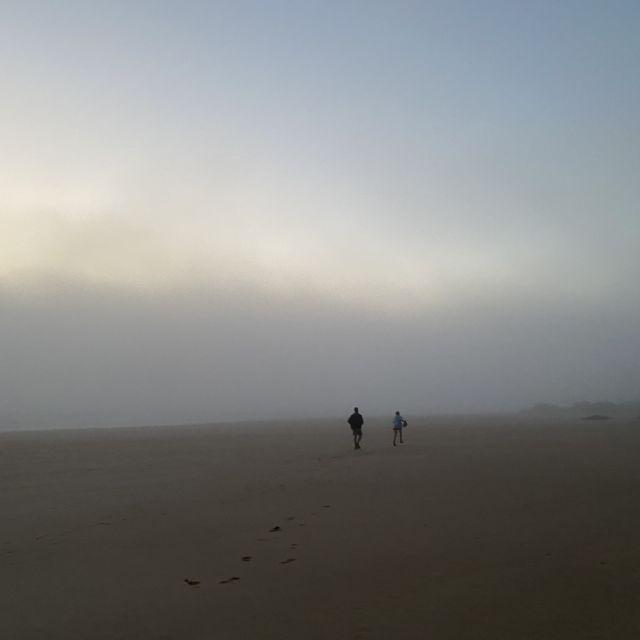 Zwei Figuren in der Ferne am Strand im Nebel