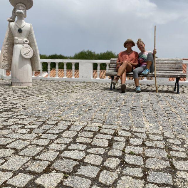 Zwei Frauen auf einer Bank neben einer Statue.