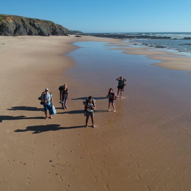 weitläufiger Strand und 5 Personen mit Wanderausrüstung.