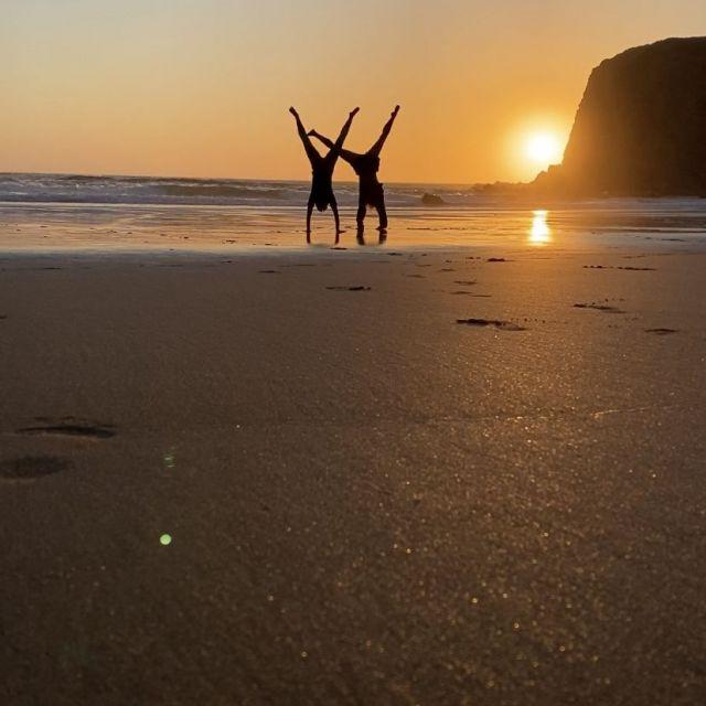 Silhuetten von zwei Frauen im Handstand am Strand.