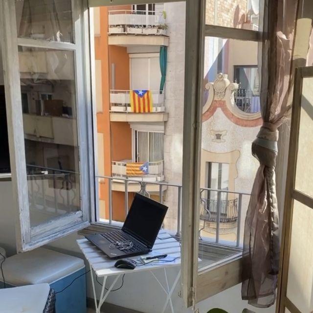 Ein Laptop, der auf einem kleinen Tisch vor einem Fenster steht.