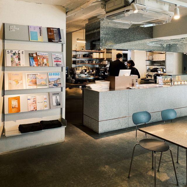 Café Interior mit grauen Stühlen und einem Regal voller Magazine