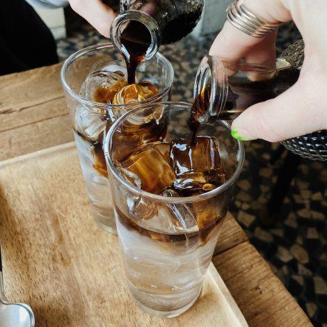 Zwei Iced Dutch Coffee, die gerade in das Glas gegossen werden