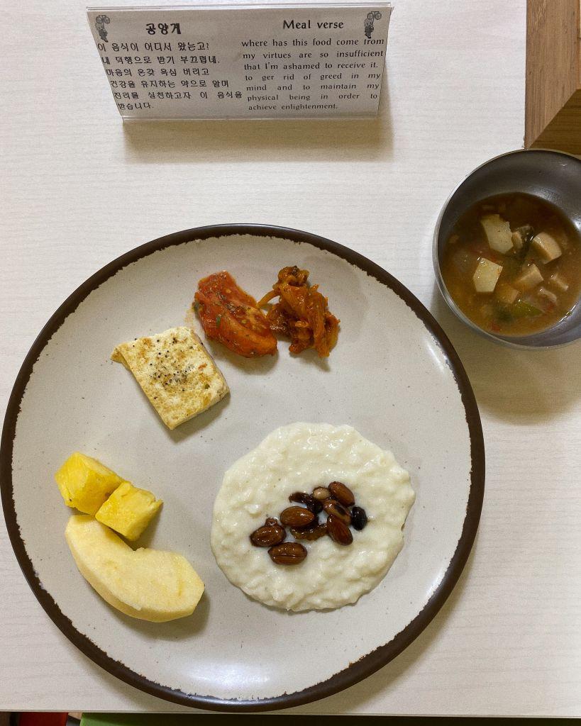 Tempelfrühstück auf dem Teller: Reisbrei, Nüsse, Obst, Tofu, Tomaten und eine koreanische 'Doenjang' Suppe