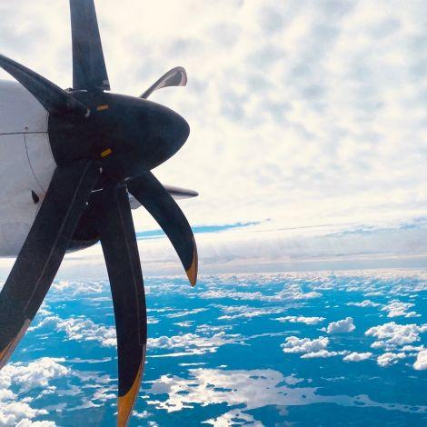 Aus dem Fenster sieht man den Propeller des Flugzeugs. Es fliegt über eine weite Seen- und Waldlandschaft.