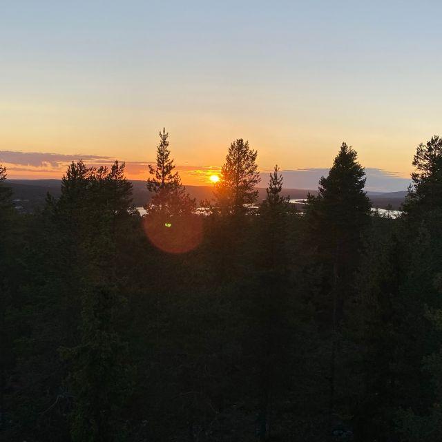 über der weiten Landschaft geht die Sonne unter.