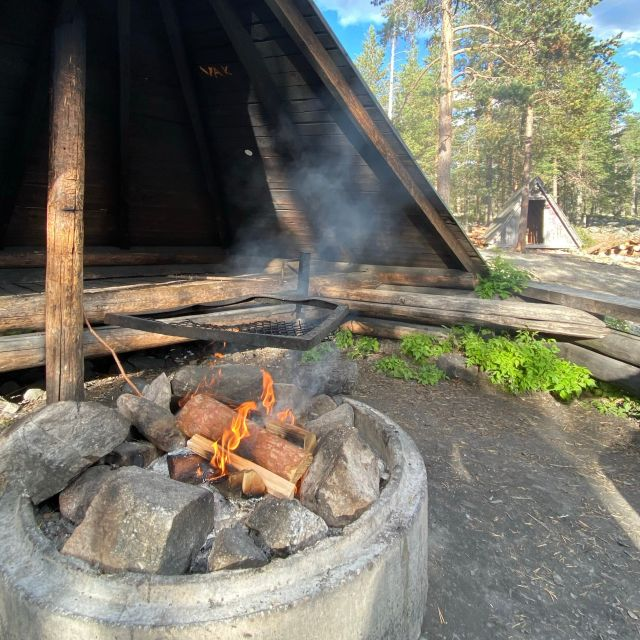 Eine Feuerstelle im Wald, an der Feuer unter dem Grillrost brennt.