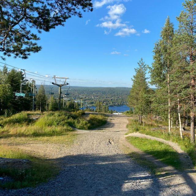 Links im Bild ist ein Skilift zu sehen, im Hintergrund der Fluss und die grüne Waldlandschaft