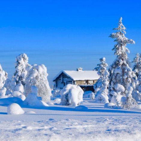Ein kleines Holzhaus in einer verschneiten Landschaft.