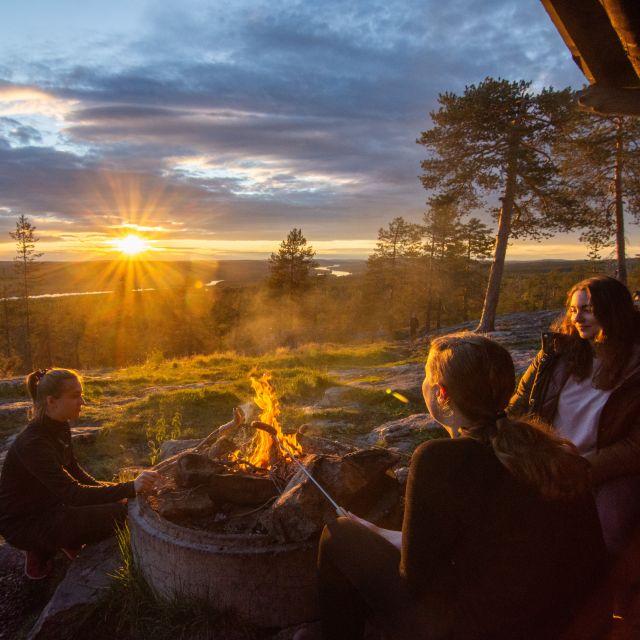 Drei Frauen sitzen in der Abendsonne am Lagerfeuer und halten Stöcker mit Stockbrot und Würstchen über das Feuer. Im Hintergrund geht die Sonne über der weiten Landschaft unter.