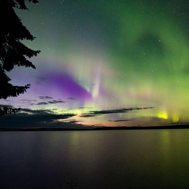 Über dem See erstrahlt der Himmel in grün und lila.