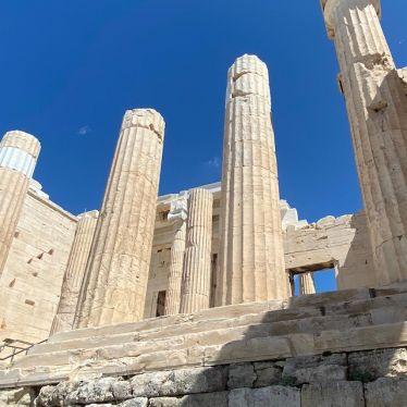 Säulen der Akropolis die in den blauen Himmel ragen.