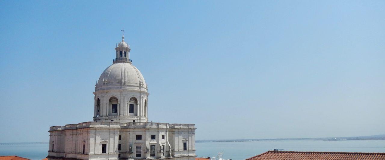 Blick auf einen weißen Turm, dahinter das Meer