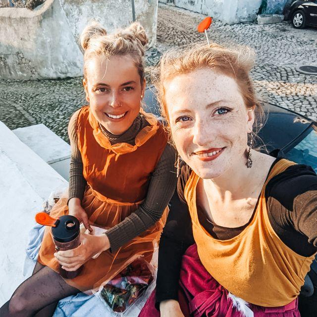 Zwei Freundinnen auf einer Mauer.