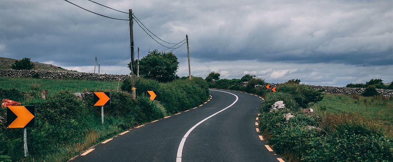 kurvige Straße umrandet von Gebüsch