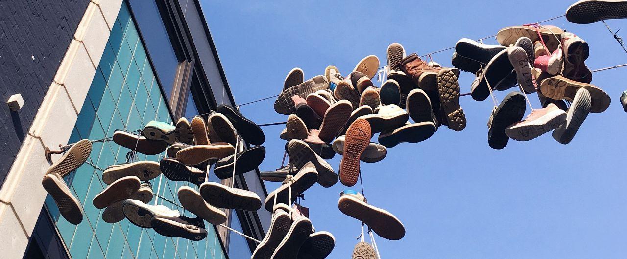 Schuhe die über einer Leine in einer Straße hängen.