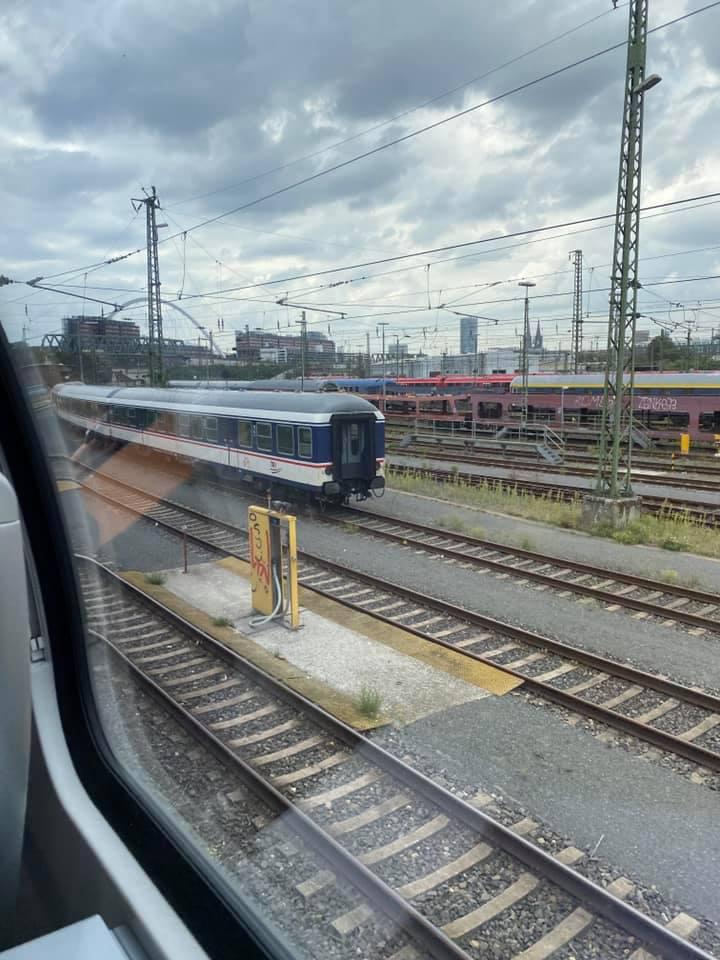 Blick aus dem Zug auf Bahngleise. Im Hintergrund erkennt man den Kölner Dom.