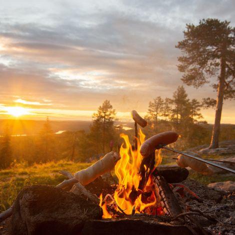 Würstchen werden auf Stöckern über dem Lagerfeuer gebraten, im Hintergrund geht die Sonne über den finnischen Wäldern unter.