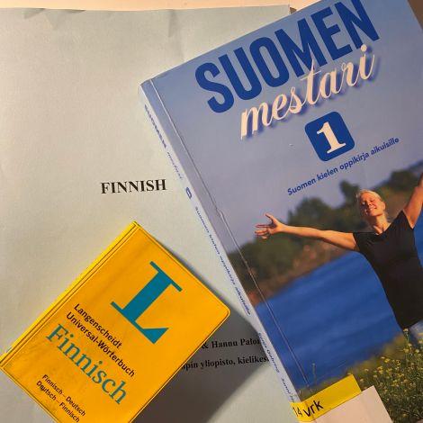 Finnisch-Lexikon und Lehrbuch liegen aufeinander.