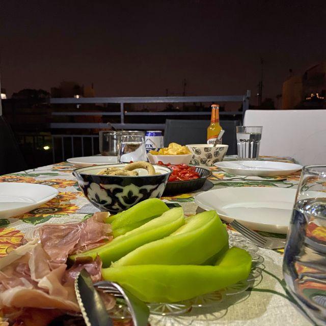 Im Vordergrund sieht man geschnittene Honigmelone und Schinken. Im Hintergrund den gedeckten Tisch mit leeren Tellern.