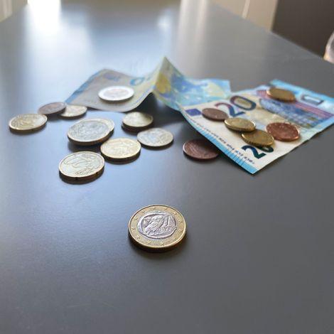 Im Vordergrund liegt eine griechische ein Euro Münze auf einem grauen Tisch. Im Hintergrund sind weitere Münzen und zwei zwanzig Euro Scheine zu sehen.