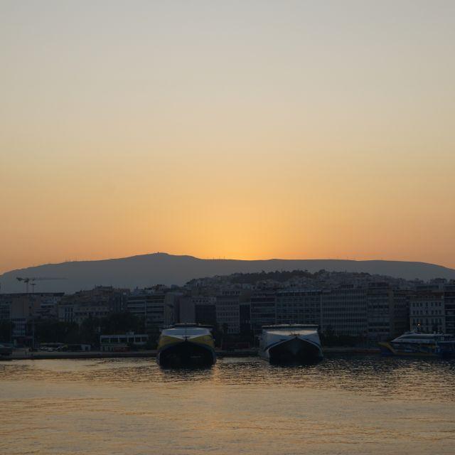 Die Abfahrt vom Piräus Hafen beim Sonnenaufgang. Boote im Meer sind zu sehen. Der Himmel ist orange.