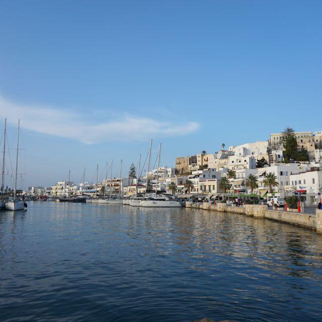 Ankunft am Hafen von Naxos. Viele Boote befinden sich im Meer. Auf der rechten Seite sieht man ein paar weiße Häuser.