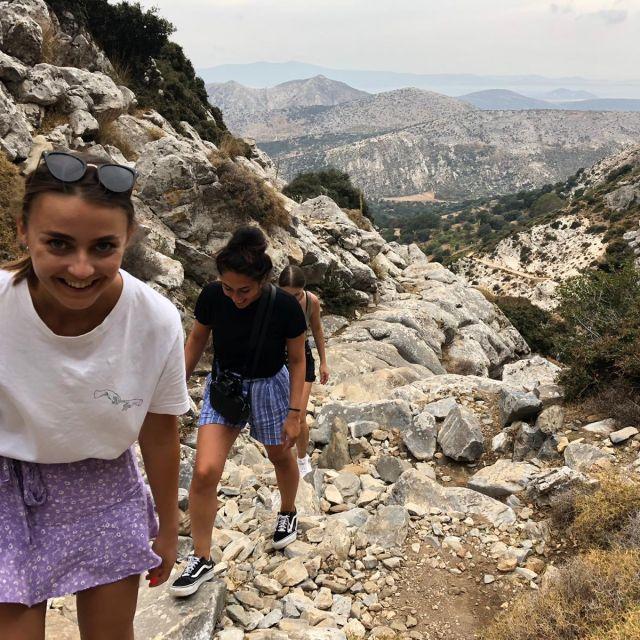 Im Vordergrund sieht man zwei Personen einen Berg hoch wandern. Im Hintergrund sieht man die Berglandschaft.