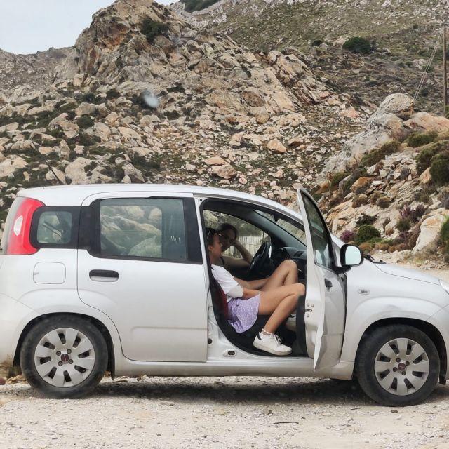 In der Mitte des Fotos sieht man ein geparktes Auto, in welchem drei Personen sitzen. Im Hintergrund eine Berglandschaft.