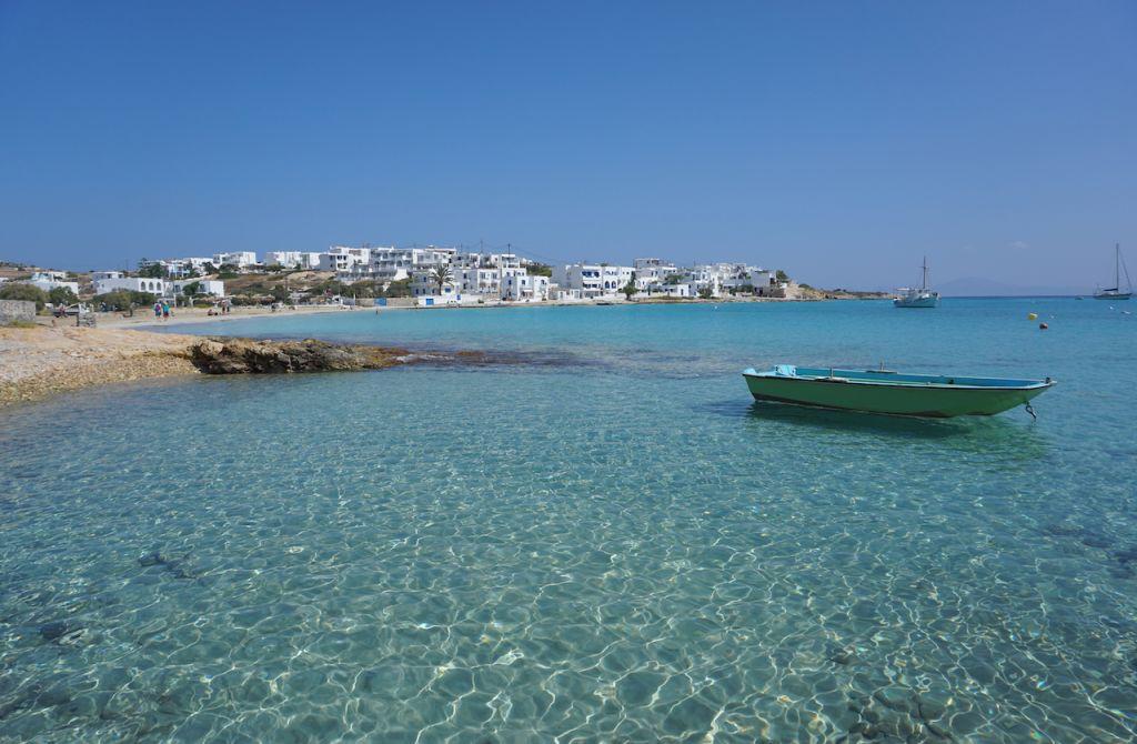 Im Vordergrund sieht man das klare und blaue Meer. Im Hintergrund die Stadt von der Insel.