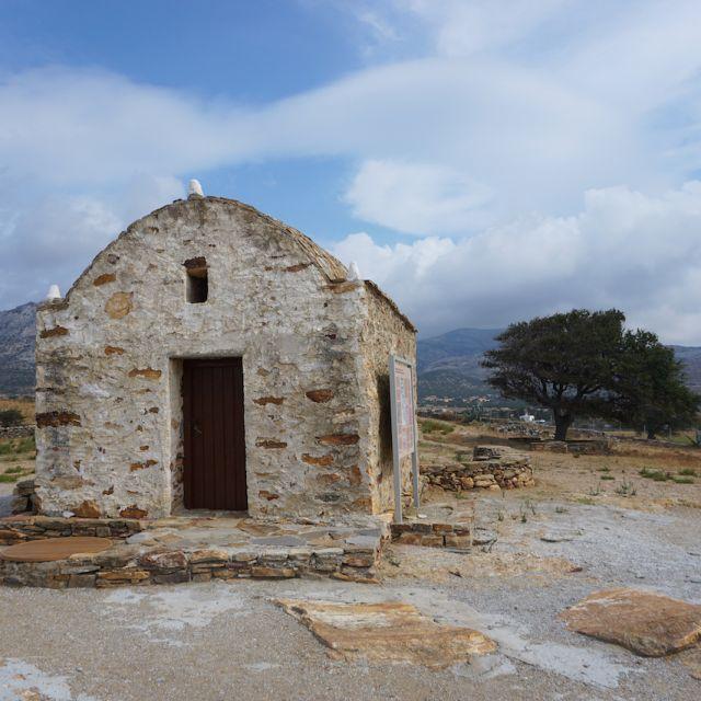 Auf der linken Seite ist eine kleine Kirche zu sehen. Auf der rechten Seite befindet sich ein Olivenbaum. Im Hintergrund eine Berglandschaft.