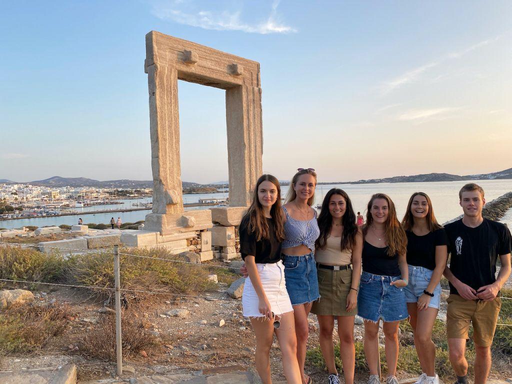 Rechts sieht man eine Personengruppe aus sechs Personen, die vor dem Tempeltor des Apollo stehen. Im Hintergrund sieht man das Meer und die Stadt von Naxos.