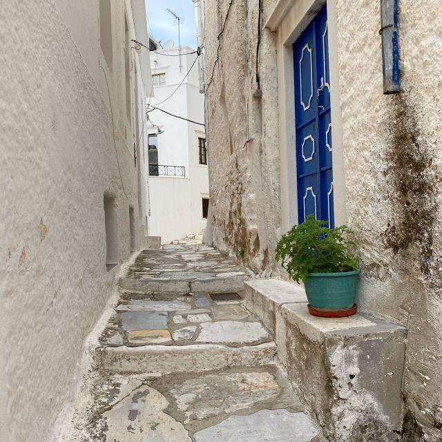 schmale Gasse durch weiße Häuser, auf der rechten Seite befindet sich eine blaue Tür.