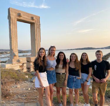 Im Vordergrund sind sechs Personen zu sehen, die für dem Tempeltor von Naxos fotografiert werden.