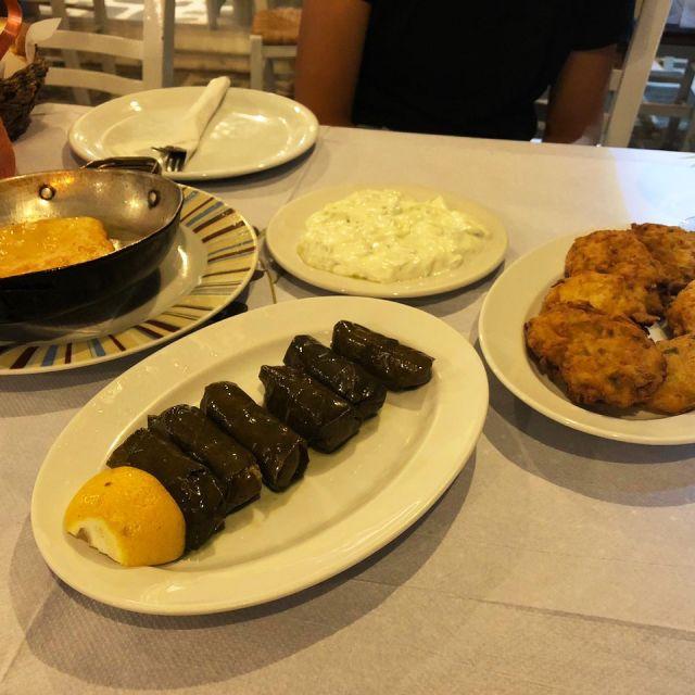 Zucchinifrikadellen, überbackener Feta und Weinblätter gefüllt mit Reis auf Tellern.