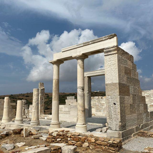 Überbleibsel des Tempels von Dimitra. Weiße und graue teils erhaltenen Säulen. Im Hintergrund sieht man den blauen Himmel mit Wolken.