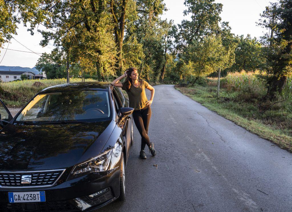 Sarah lehnt an Auto