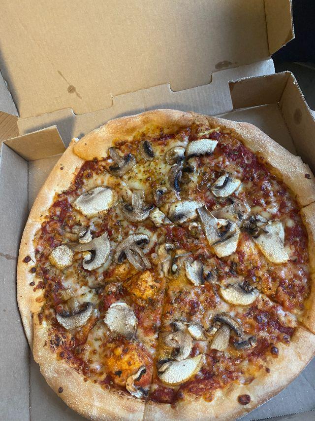 Auf dem Bild sieht man eine Pizza Funghi.
