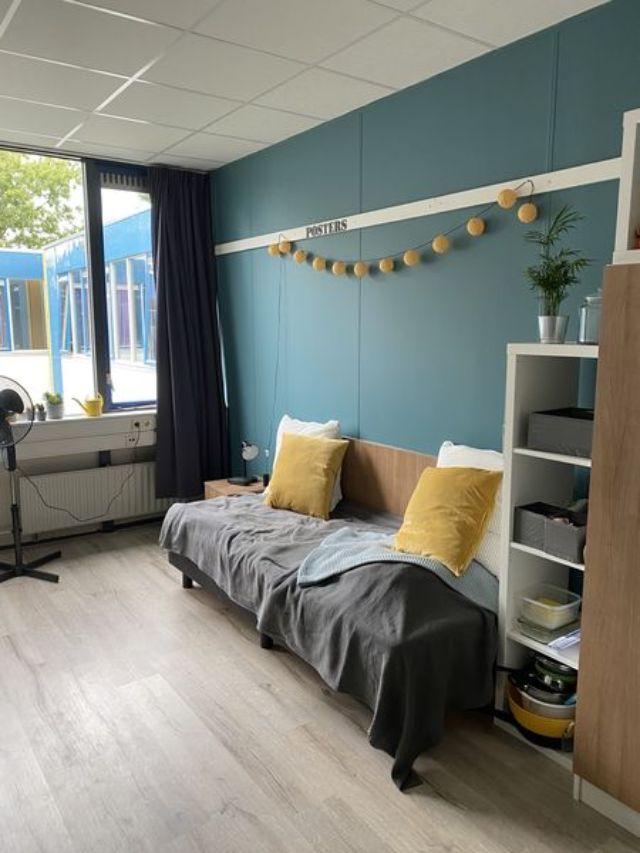 Man sieht ein Zimmer mit Bett und Tagesdecke. Über dem Bett hängt eine gelbe Lichterkette. Die Wände sind blau.